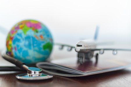 Healthcare and travel insurance concept. Stethoscope , passport document, airplane and globe Archivio Fotografico