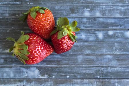 Strawberries on blue wooden table Banco de Imagens