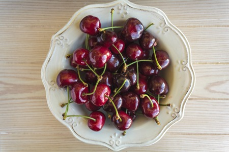 Bowl of cherries on wooden table. Top view