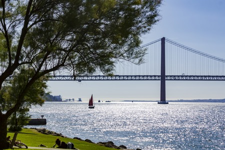 Young girl lying in a park by the river in a beautiful sunny day with sailboat and suspension bridge on the background Banco de Imagens
