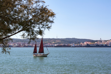 Sailboat on river with city on the background