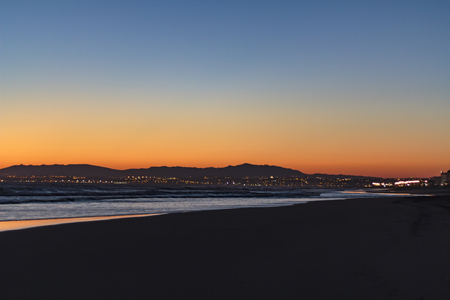 Beach and city lights at sunset