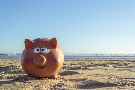 Piggy bank on beach. Save money for vacation concept