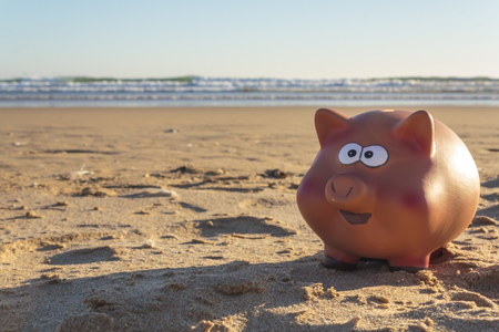 Piggy bank with beach on the background. Holidays concept