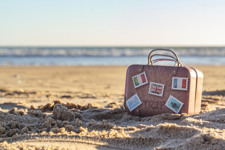 Travel suitcase on beach with copy space. Vacation concept