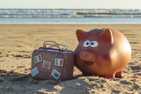 Piggy bank and travel luggage on beach