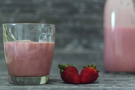 Glass with strawberry milkshake, strawberries and bottle on the background
