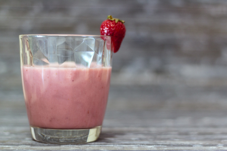 Glass with natural strawberry milkshake on rustic background