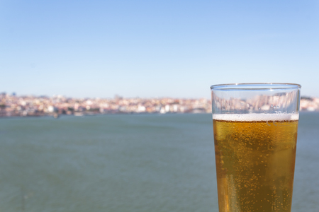 Glass of beer with sea and city in the background