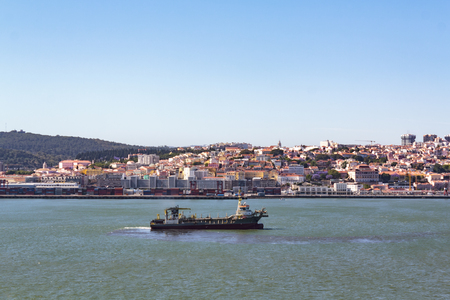 Cargo ship on water with city on the background Banco de Imagens