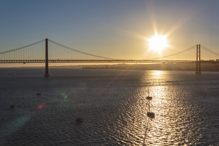Sailboats on river with April 25th Bridge on the background at sunset