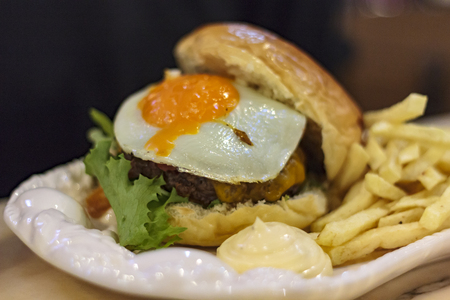 Meat Burger with Egg and french fries with sauce on a plate