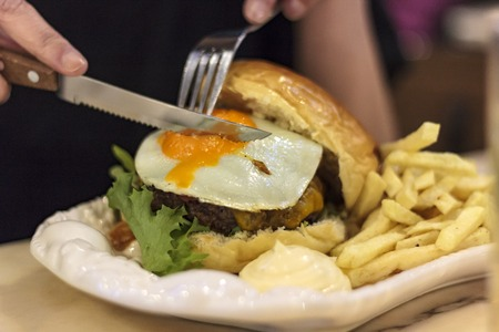 Woman eating meat hamburger with knife and fork Banco de Imagens