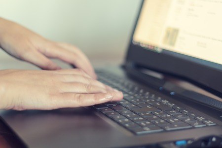 Womans hands typing on laptop keyboard