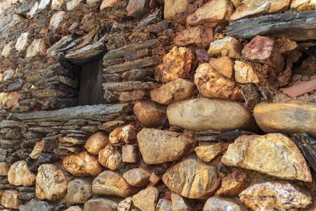 Old window on schist facades dotted with round stones from the river