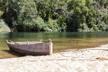 Wooden boat moored by the river Фото со стока