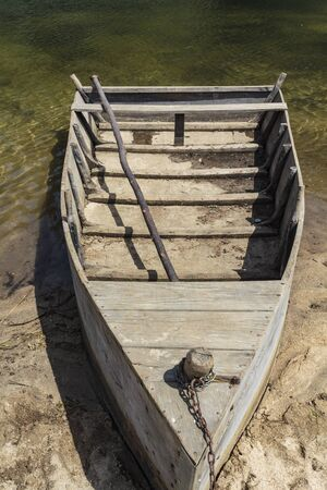A small wooden boat that transports people, animals and goods from one bank of the river to the other Фото со стока