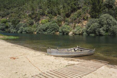 Wooden boat at river beach in Janeiro de Baixo, Portugal Фото со стока