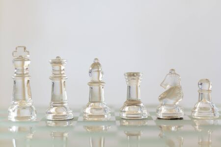 Set of chess pieces standing in line on chessboard Фото со стока