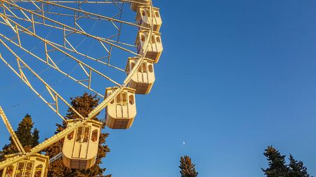 Ferris wheel at evening with moon visible