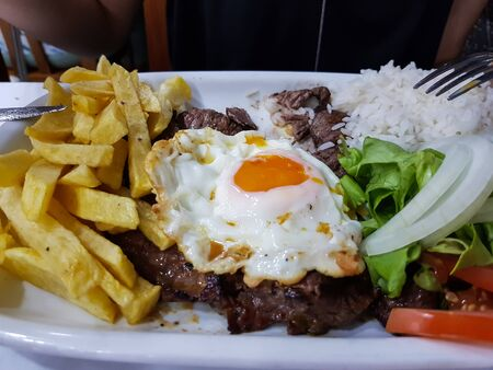 Portuguese cuisine, beef with fried egg and french fries 免版税图像