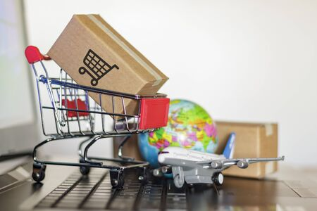 Shopping cart with cartons, globe and airplane on computer. Online shopping, e-commerce and worldwide delivery business concept