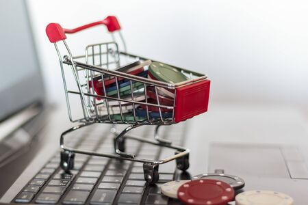 Poker chips in a trolley on a laptop keyboard. Online Gambling addiction concept