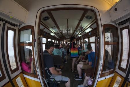 People inside a famous yellow tram in Lisbon Редакционное