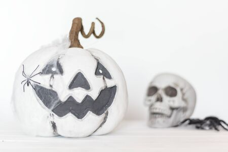 Scary white pumpkin with cobweb and spider and skull on the background. Halloween concept Фото со стока