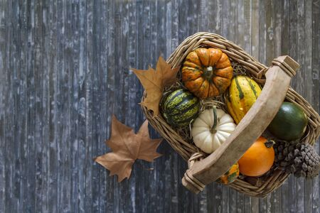 Top view of pumpkins in wicker basket and dry leaves on blue background