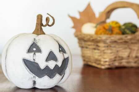 Halloween pumpkin on wooden table and basket with pumpkins on the background