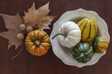 Top view of assortment of pumpkins and dry leaves on wooden table Фото со стока