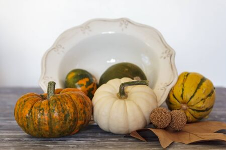 Assortment of pumpkins and vintage bowl