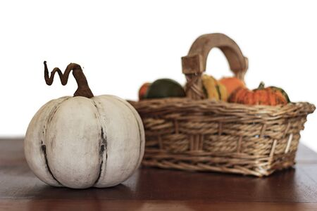 White pumpkin on wooden table with assortment of pumpkins on basket on the background