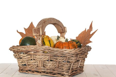 Different kinds of pumpkins and mapple dry leaves on wicker basket