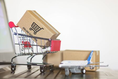 Shopping cart with cartons and airplane on computer. Online Shopping and International shipping concept