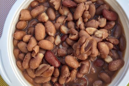Top view of bowl with baked beans in the oven. Portuguese cuisine