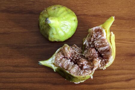 Fresh whole and cut figs on wooden table