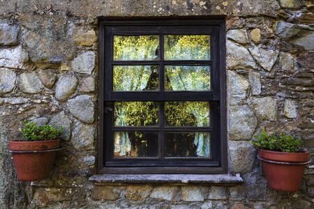 Window with curtains and vases in stone house