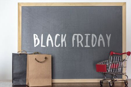 Shopping bags and trolley with blackboard on the background with the word Black Friday. Black Friday season sales concept Stok Fotoğraf