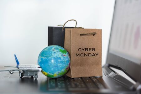 Shopping bags with world globe and airplane on laptop. Worldwide online shopping, Cyber monday season concept