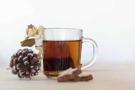 Cup of tea decorated with sweet angel, pine cone and cookies on white wooden table