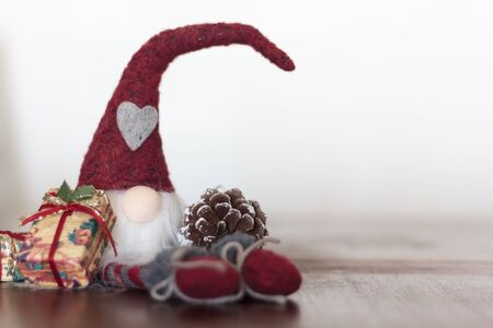 Christmas gnome with gift and pine cone. With copy space