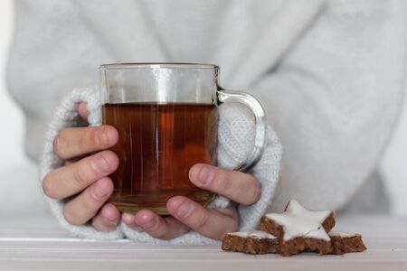 Woman hands holding a cup of tea with cookies on the side