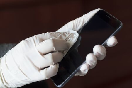 Hands with gloves cleaning and disinfecting mobile phone. Germs, bacteria, Covid-19 Contamination