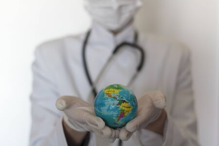 Doctor with gloves holding world globe in her hands. Universal healthcare concept