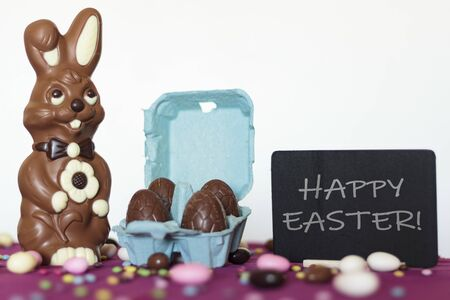 Chocolate bunny, egg carton with chocolate eggs and blackboard with the text Happy Easter
