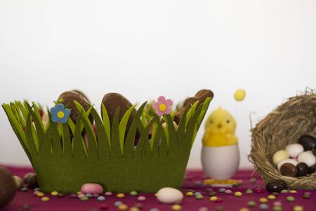 Easter basket with chocolate eggs, decorative chick, bird nest with easter almonds and other sweets on table