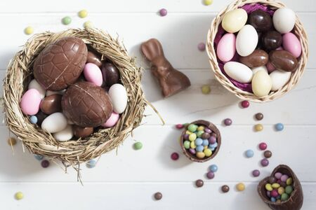 Top view of Chocolate eggs on nest, chocolate bunny, easter almonds and sweets on white wooden table. Easter composition