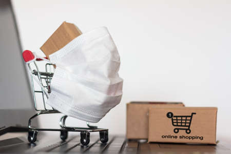 Shopping cart and carton boxes on laptop. Online shopping in isolation or quarantine, Coronavirus Covid-19 pandemic